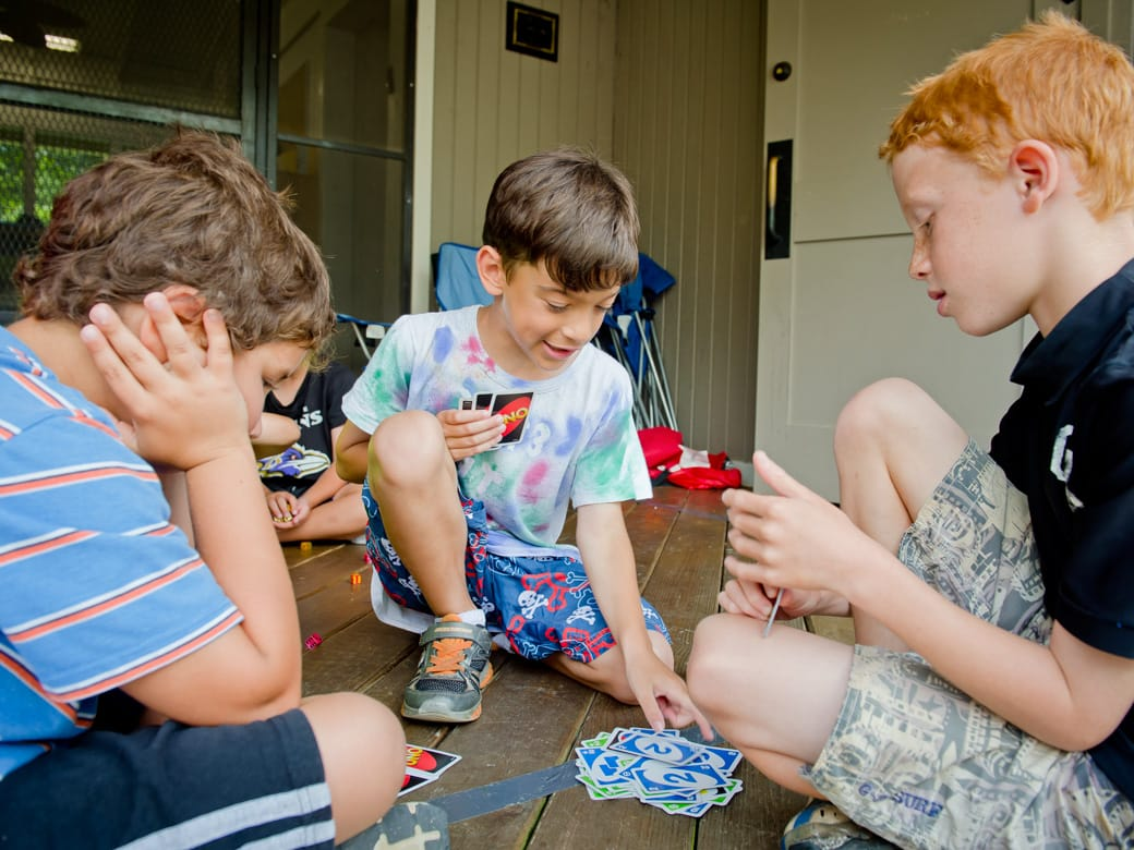 Airy campers playing cards in bunk