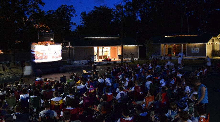 Airy campers watching an outdoor movie
