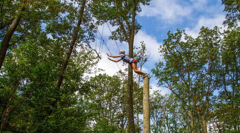 Girl jumping off pole at high ropes course