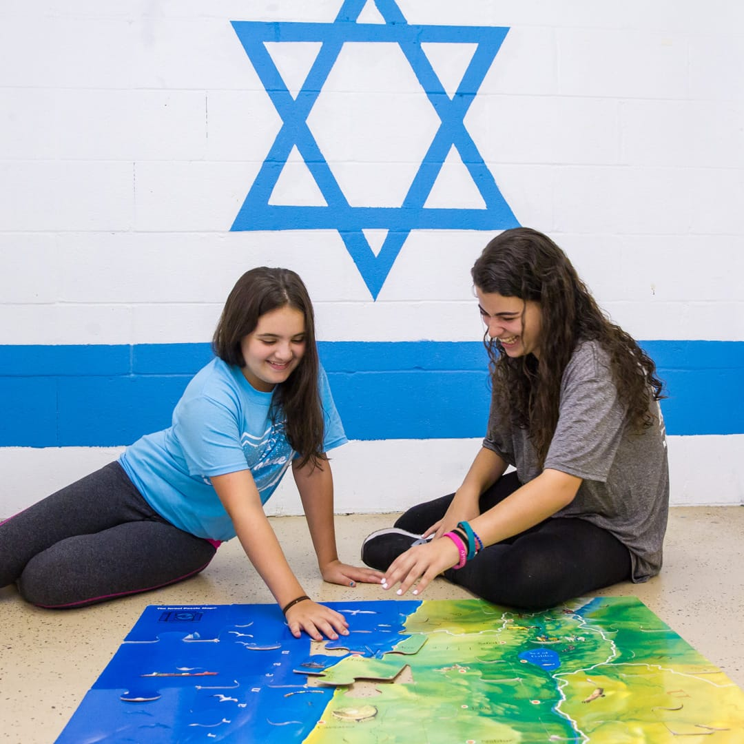 Girls doing a puzzle of Israel
