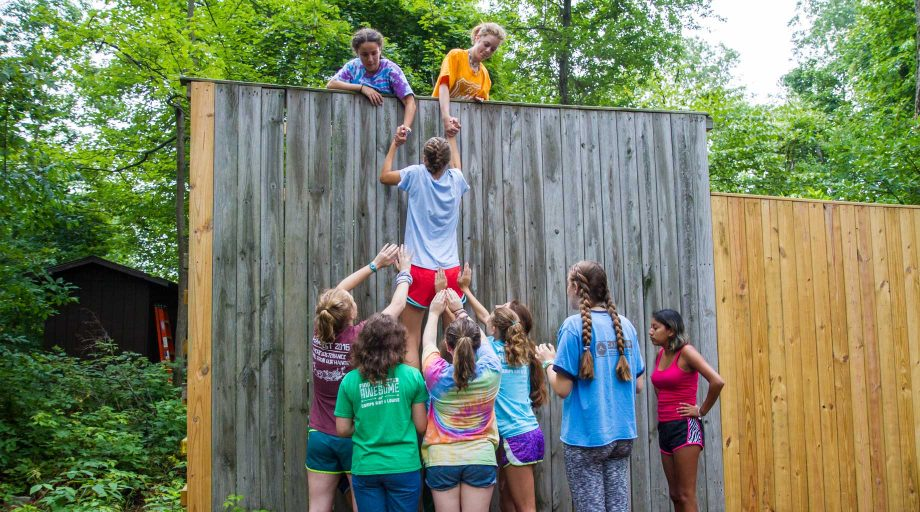Campers doing team-building activities on low ropes course