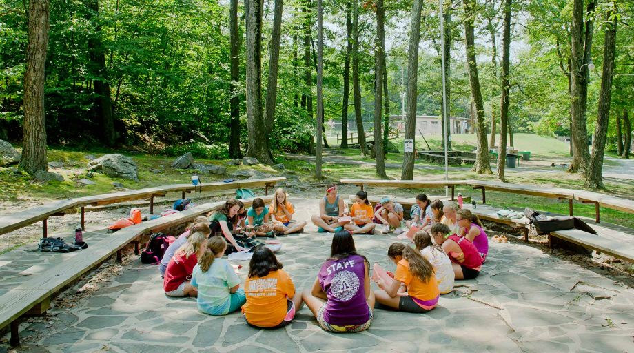 Campers sitting outdoors in a circle playing music