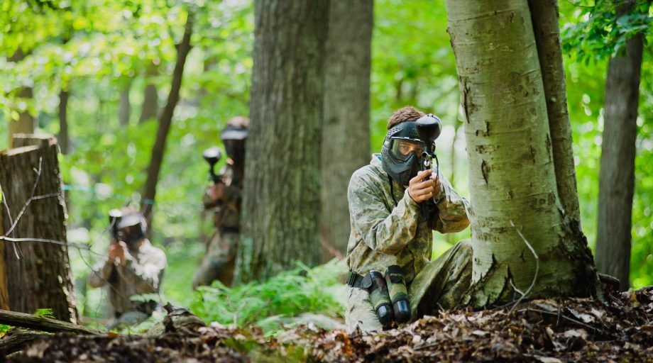 Campers playing paintball in the woods