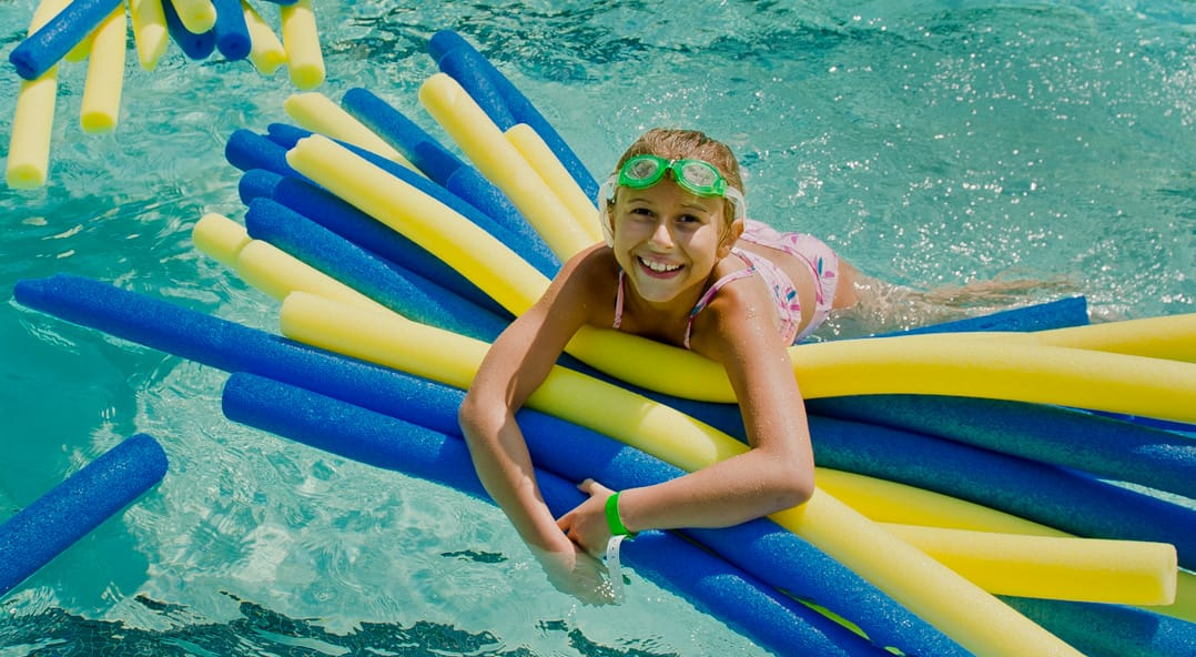 Louise camper in the pool with a bundle of pool noodles