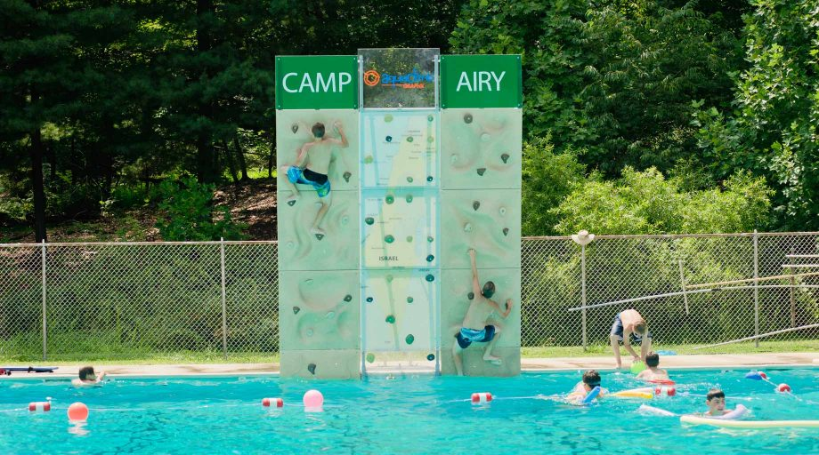 Airy campers climbing rock wall by pool