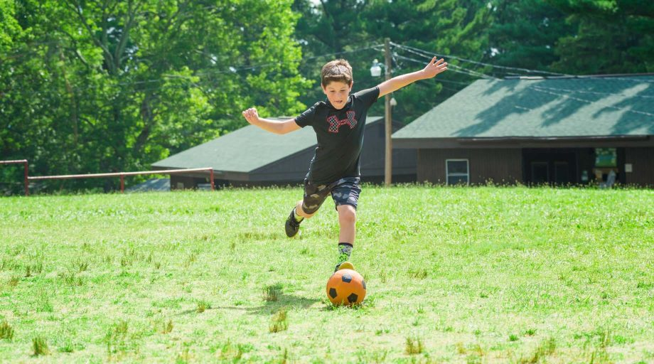 Camper kicking a soccer ball