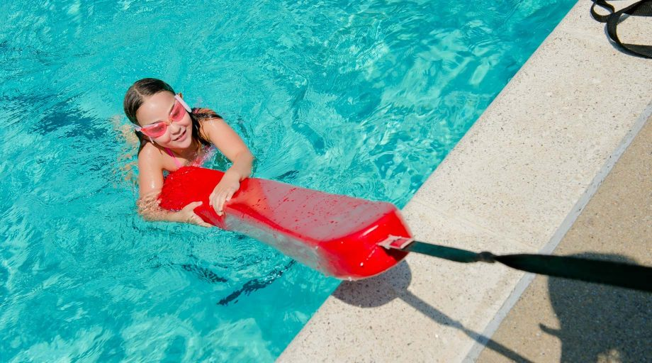 Girl holding onto lifeguard floatation device