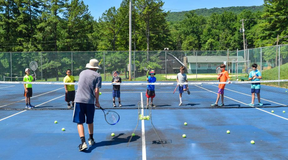 Campers learning how to serve at tennis